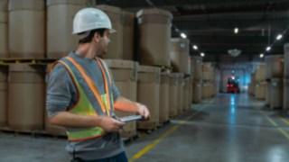 Un employé porte la veste de sécurité interactive Fenwick-Linde dans un entrepôt sombre