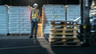 Un employé d'entrepôt et un chariot élévateur se croisent. Ce piéton est bien visible grâce à la veste de sécurité interactive Fenwick-Linde