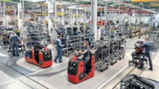 Des tracteurs avec plusieurs supports de marchandises transportent les composants jusqu'à la ligne de production.