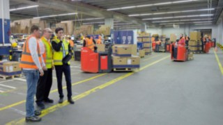 Trois personnes analysent les particularités d'un atelier d'usine.